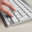 Female hand with keyboard on wooden desktop background — Stock Photo #63467613