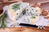 Blue cheese with sprigs of rosemary and nuts on board with knife and wooden table background — Stock Photo