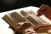 Hands of old woman with Bible on table and dark background — Stock Photo