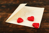 Empty envelope with hearts on rustic wooden table background — Stockfoto