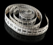 Measuring tape on black background — Stock Photo