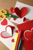 Beautiful hand made post cards, pens and scissors  with paper hearts on color wooden background — Stock Photo