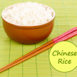 Bowl of rice with chopsticks on bamboo mat and space for your text — Stock Photo #63529479