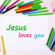 Jesus loves you text on paper on table background — Stock Photo #63529843