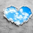 Blue sky background with clouds through heart shaped hole in paper — Stock Photo #63529983