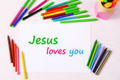 Jesus loves you text on paper on table background — Stock Photo