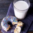 Crumbled donut on napkin with glass of milk on rustic wooden planks background — Stock Photo #63535699