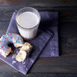 Crumbled donut on napkin with glass of milk on rustic wooden planks background — Stock Photo #63535711