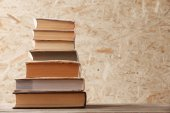 Stack of books on wooden hardboard background — Stock Photo