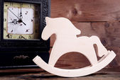 Retro clock with decorative horse on table on wooden background — Stock Photo