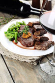 Steak on plate with bottle of wine on wooden background — Stock Photo