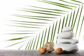 Still life of spa stones on bamboo mat surface with palm leaf isolated on white — Stock Photo