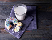 Crumbled donut on napkin with glass of milk on rustic wooden planks background — Stock Photo