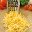 Grated cheese with grater and vegetables on wooden cutting board and white background — Stock Photo #63675711