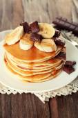Stack of delicious pancakes with chocolate, honey and slices of banana on plate and napkin on wooden table background — Stock Photo