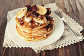 Stack of delicious pancakes with chocolate, honey, nuts and slices of banana on plate and napkin on wooden table background — Stock Photo