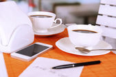 Two cups of coffee with pen and phone number on napkin on table with orange bamboo mat, on light background — Stock fotografie