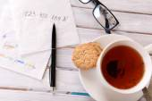 Cup of coffee with glasses, pen and business notes on napkin on wooden table background — Foto Stock