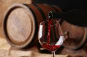Pouring red wine from bottle into glass with wooden wine casks on background — Stock Photo