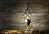 Kerosene lamp with hay on rustic wooden planks background — Stock Photo