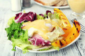 Toast with egg Benedict and greens on plate on wooden table — Stock Photo