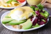 Toast with egg Benedict and avocado on plate on wooden table — Stock Photo