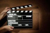 Movie clapper in female hand on wooden background — Stock Photo
