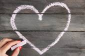Hand draws heart of chalk on wooden board — Stock Photo