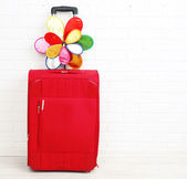 Red suitcase with toy flower on white brick wall background — Stock Photo