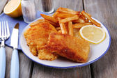 Breaded fried fish fillets and potatoes with with sliced lemon and cutlery on plate and wooden planks background — Stock Photo