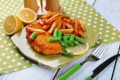 Breaded fried fish fillets and potatoes with asparagus and sliced lemon on plate and wooden planks background — Stockfoto