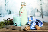 Fresh milk with natural decor, on wooden table, on winter background — Stock Photo