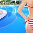 Young woman with slim body in swimsuit on swimming pool background — Stock Photo #63768173