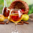 Apple cider in wine glass and bottle, with cinnamon sticks and fresh apples on wooden table, on bright background — Stock Photo #63837153