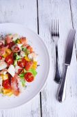 Fresh fish salad with vegetables on plate on wooden table close-up — Foto de Stock