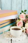 Cup of tea with books and flowers on wooden background — Stock Photo