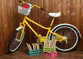 Bicycle with books in crate on wooden wall background — Stock Photo