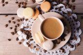 Нежные красочные миндальные печенья и кофе в кружке на деревянном фоне стола — Стоковое фото