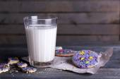 Crumbled glazed cookies on sheet of paper with glass of milk on rustic wooden planks background — Stock Photo
