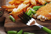 Breaded fried fish fillet and potatoes with asparagus on wooden cutting board background — Stock Photo