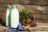 Bottles of fresh milk with natural decor, on wooden background — Stock Photo