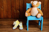 Bear toy on chair on wooden background — Stock Photo