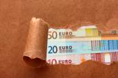 Euro banknotes through torn craft paper — Stok fotoğraf