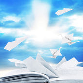Origami airplanes on book on sky bakground — Stock Photo