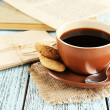 Cup of coffee with spoon and cookies on burlap cloth near envelopes on color wooden background — Stock Photo #63956389
