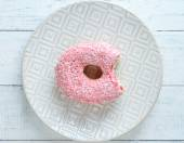 Bitten delicious donut on plate on wooden table close-up — Stock Photo