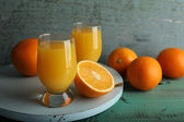 Glass of orange juice with slices on color wooden background — Photo