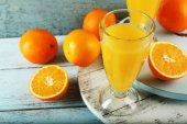 Glass of orange juice with slices on color wooden background — Stock fotografie
