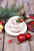 Delicious cake on saucer with holly and berry on Christmas decoration and wooden background — Stok fotoğraf