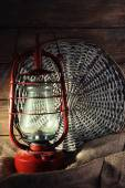 Kerosene lamp with wicker mat and burlap cloth on wooden planks background — Stock Photo